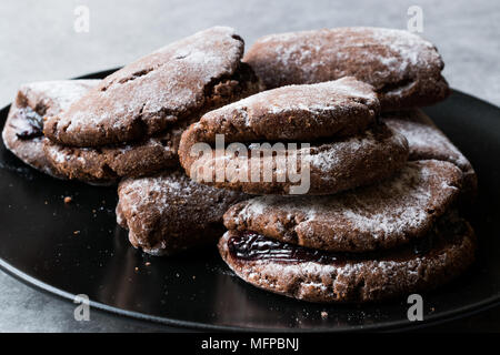 Jelly Filled Chocolate Cookies with Powdered Sugar and Cherry Jam. Dessert Concept. - Stock Photo