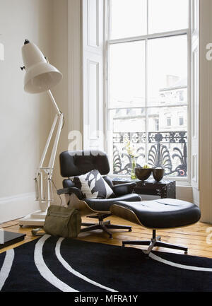 Oversize anglepoise floor lamp behind Eames lounge chair and ottoman in front of window - Stock Photo