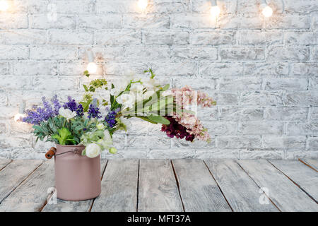 Flowers with light bulbs on white brick background with wooden floor - Stock Photo