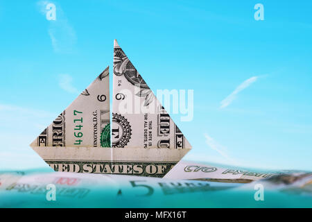 Boat made from a one-dollar bill floats in the ocean among other currencies - Stock Photo