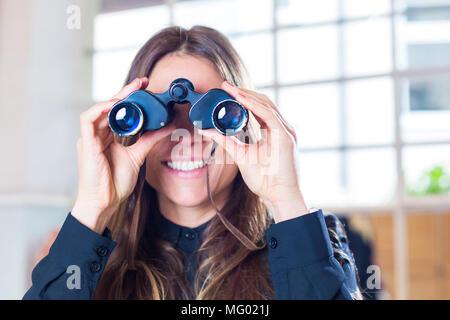Deutschland, München, Portrait Geschäftsfrau im Büro durch Fernglas schauend - Stock Photo