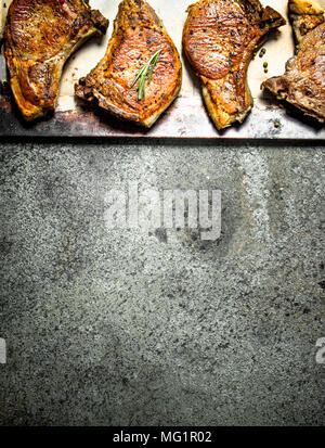 The pork steak with spices. On rustic background. - Stock Photo