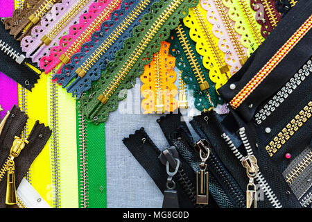 a lot of bright colored zippers for clothes in the store. Abstraction, a photo as a background - Stock Photo