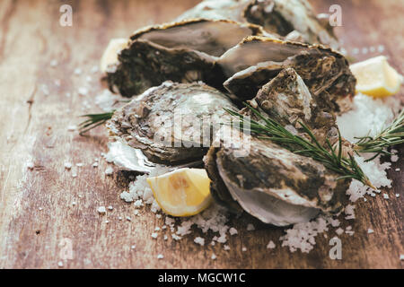 Open shell oyster with lemon and salt on a wooden board - Stock Photo