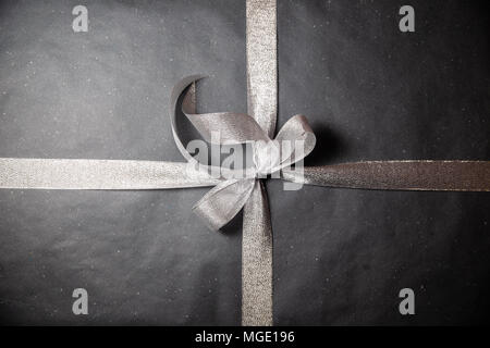 Black gift box with silver ribbon - Stock Photo