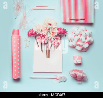 Fresh beautiful flowers bunch in envelope with greeting accessories: bow, ribbon, gift paper, pen and shopping bag on pastel blue desktop background,  - Stock Photo