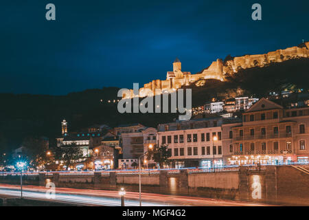 Tbilisi, Georgia. Narikala Ancient Fortress In Evening Night Illumination Under Blue Sky. - Stock Photo