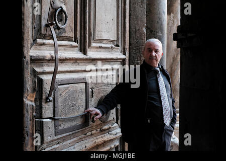 Wajeeh Nuseibeh, a Muslim whose family has opened and closed the Holy Sepulcher since the Ottoman era posing at the doors of the church of Holy sepulchre in old city East Jerusalem Israel. The custody of the door and the key for the Church of the Holy Sepulchre is entrusted to two Muslim families (Nuseibeh and Judeh) and it has been like this for centuries. - Stock Photo