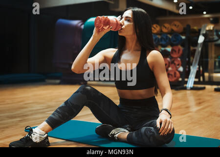 Young attractive brunette girl relaxing and drinking water at gym on the blue yoga mat after workout. - Stock Photo