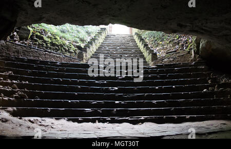 Stairs of a cave entrance, very dark and wet low light muddy very much risky to walk on it. The cave is built of stone. Light cant reach into it. Brig - Stock Photo