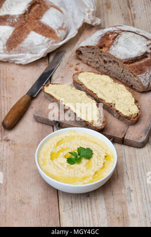 Sourdough bread and spelt sourdough bread with homemade hummus on a bread board. UK. UK - Stock Photo