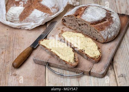 Sourdough bread and spelt sourdough bread with homemade hummus on a bread board. UK - Stock Photo