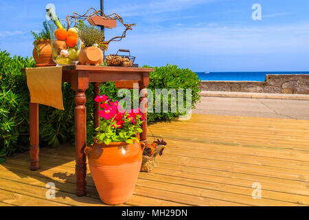 Pot with flowers and restaurant table decorated with vegetables on wooden deck along seashore in small village near Cala Ratjada, Majorca island, Spai - Stock Photo