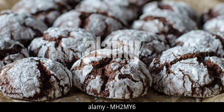 Chocolate crinkle cookies with powdered sugar icing. Cracked chocolate biscuits. close up - Stock Photo