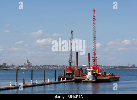 Marine construction barges with cranes for pile driving. Marina Bay, Quincy, MA. - Stock Photo