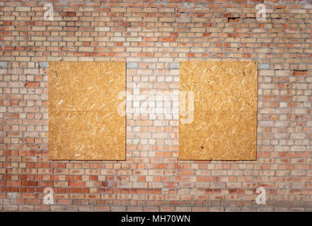 Unfinished red brick house wall with chipboard wood covered windows. - Stock Photo