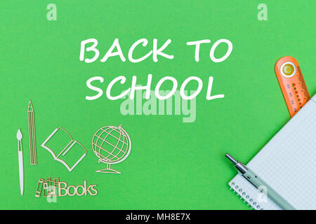 concept school, text back to school, school supplies, notebook, ruler and pen on green backboard - Stock Photo