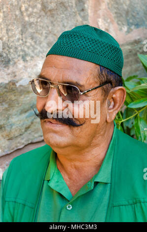 KUMBHALGARH, INDIA - NOVEMBER 21, 2016: Middle aged Indian muslim man with mustache, wearing dark glasses near Kumbhalgarh Fort Palace in Rajasthan. - Stock Photo