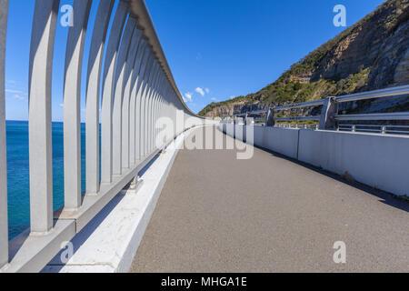 Curved walkway with metal railing along coastal bridge in Australia - Stock Photo