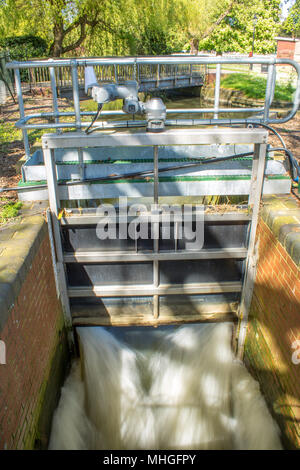A metal lock gate with water from the River Great Ouse gushing through at Bedford - Stock Photo