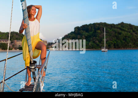 Sailing boat crew on rest. Happy young woman on deck of charter yacht, have fun discovering islands, travel in tropical sea on summer cruise. - Stock Photo