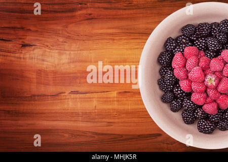 Plate with berries on the wooden table - Stock Photo
