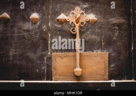 Brass door knocker on a dark wooden door. Landscape format. - Stock Photo