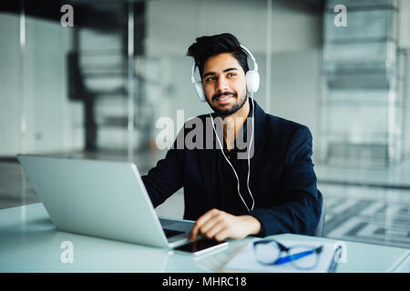 Young businessman working with laptop computer and headphone in the office, symbolizing customer support - Stock Photo
