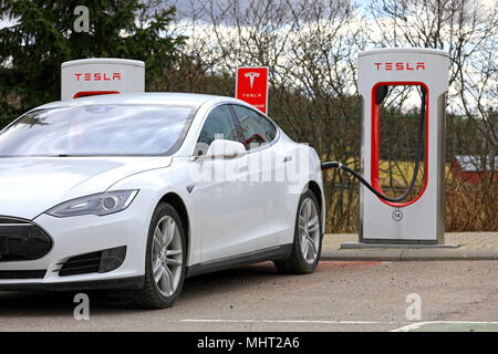 White Tesla Model S electric car connected and charging at Supercharger station on a day of spring in Paimio, Finland - April 28, 2018. - Stock Photo