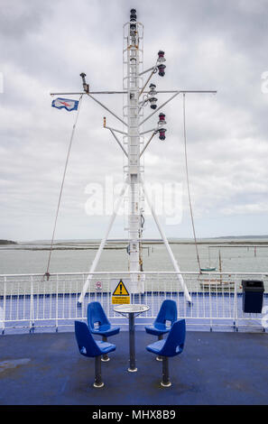 Table and chairs on the deck of a Wightlink feery between Lymington, Hampshire and Yarmouth, Isle of Wight. - Stock Photo