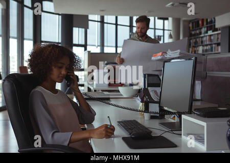 Female architect talking on phone while colleague checking blueprint - Stock Photo