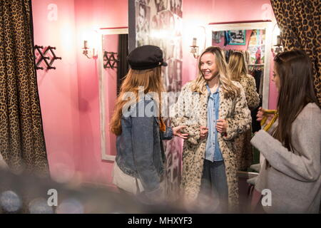Friends trying on vintage clothes in thrift store - Stock Photo