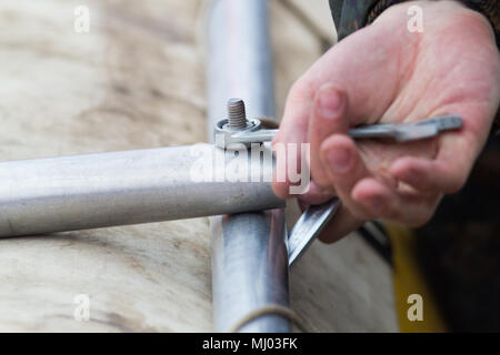 Male hand bolting the metal paddles with wrench - Stock Photo