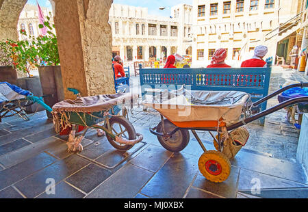 The street scene in Souq Waqif with old wheelbarrows of local porters on the foreground, Doha, Qatar. - Stock Photo