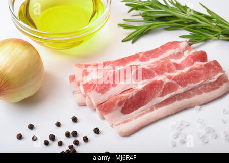 Raw bacon slices with condiments on white background - Stock Photo
