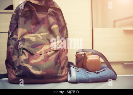 Travel background concept, hipster bag with retro camera case on jeans jacket on bed with free copy space. - Stock Photo
