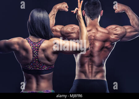 Couple of athletes posing in front of the camera showing their athletic backs and hands on a black background - Stock Photo
