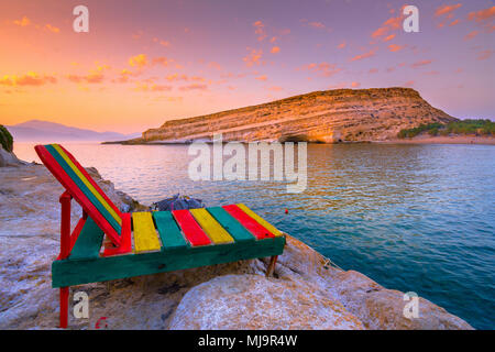 Matala beach with caves on the rocks that were used as a roman cemetery and at the decade of 70's were living hippies, Crete, Greece. - Stock Photo