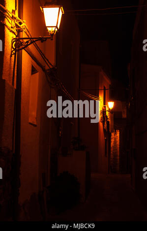 Orange streetlights in an alley in a small Sardinian village - Stock Photo