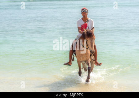 Indonesian man riding a horse in the blue and green water on the beach towards the camera, april 24, 2018, Gili Trawangan, Indonesia - Stock Photo