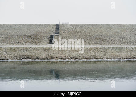 bench made of metal on a dike with stairs, winter, sky grey white, waters in foreground - Stock Photo