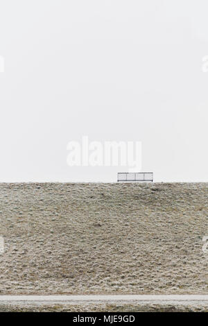 bench made of metal on a dike in winter, sky grey white, road with hoarfrost - Stock Photo