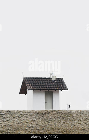 small house on a dike in winter, sky grey white, hoarfrost - Stock Photo