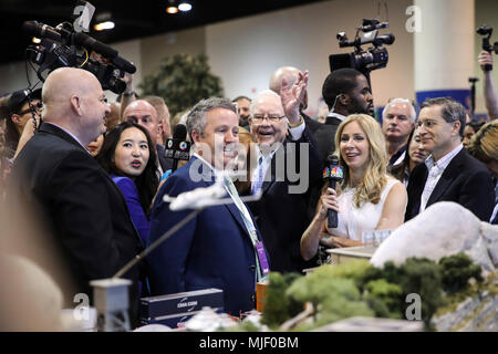 Omaha, USA. 5th May, 2018. U.S. billionaire investor Warren Buffett (C), chairman and CEO of Berkshire Hathaway, greets people as he visits an exhibition on his invested companies before the Berkshire Hathaway's annual shareholders meeting in Omaha, Nebraska, the United States, on May 5, 2018. Berkshire Hathaway held its 2018 shareholders meeting on Saturday, attended by tens of thousands of people from all over the world. Credit: Wang Ying/Xinhua/Alamy Live News - Stock Photo