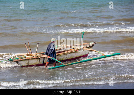 A lone Filipino fisherman heads out to sea in his one-man bangka (paraw - parao), a home-made boat with two bamboo outriggers off Baybay Beach on the  - Stock Photo