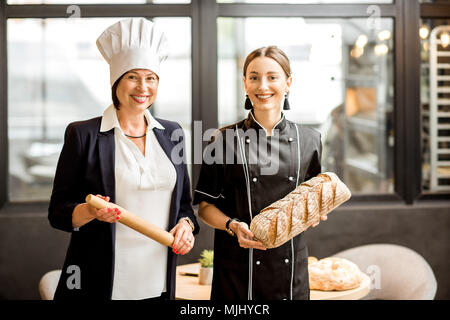 Senior chef confectioner with young assistant in the bakery shop - Stock Photo