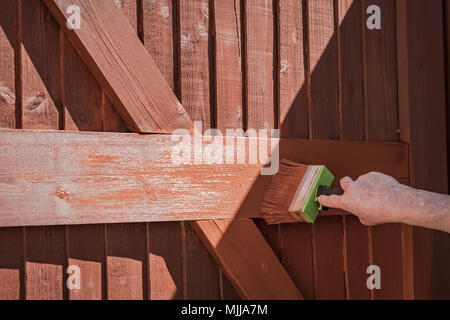 Woman seen painting a timber built gated entrance with a large, timber paintbrush. This shallow focus image is of the paint brush. - Stock Photo