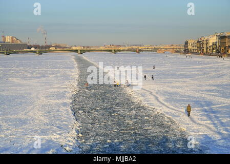ST.PETERSBURG, RUSSIA - MARCH 07, 2018:  People walk along the frozen fairway, punched by an icebreaker on the Neva river against the Trinity bridge o - Stock Photo
