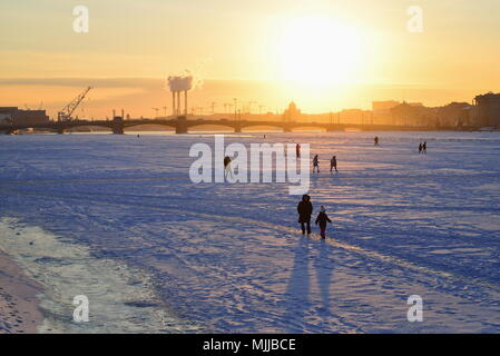 ST.PETERSBURG, RUSSIA - MARCH 07, 2018:  View of the Annunciation bridge, people on the ice of the Neva river and the sunset from Admiralty embankment - Stock Photo