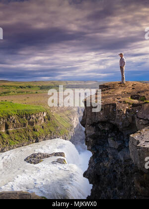 Young man standing on the edge of a cliff looking out at the horizon, over a waterfall against a dramatic cloudy sky, Gullfoss, Iceland - Stock Photo